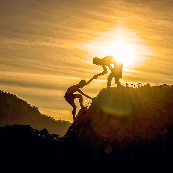 Une personne en aide une autre pour franchir un obstacle